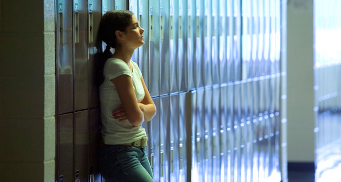 Girl-standing-against-lockers